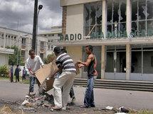 Devant le siège de la radio nationale incendié par des émeutier, des Malgaches nettoient des débris, le 29 janvier 2009.( Photo : Reuters )