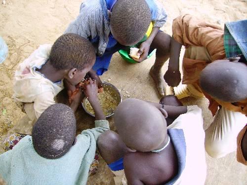 des jeunes talibés qui sont en train de manger dans la rue