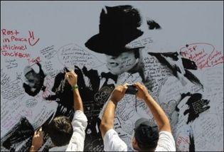 Des fans de Michael Jackson inscrivent des hommages sur le portrait géant de leur idole le 6 juillet 2009 à Staples Center à Los Angeles (Photo: AFP)