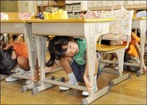 Des enfants se cachent sous une table lors d'un exercice anti-sismique, en septembre 2008.(photo archive AFP)