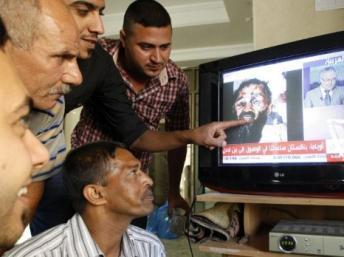A Bagdad, des Irakiens regardent la chaîne de télévision Al-Arabiya qui diffuse des images du cadavre d'Oussama ben Laden, le 2 mai 2011. PHOTO/SABAH ARAR