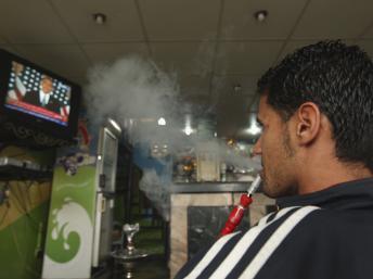 Un Libyen à Benghazi fume son narguilé en regardant le discours de Barack Obama à la télévision, le 19 mai 2011. REUTERS/Mohammed Salem