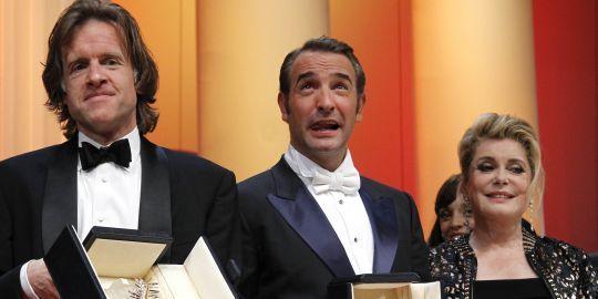 """De gauche à droite : le producteur américain Bill Pohlad pour """"The Tree of Life"""", de Terrence Malick, l'acteur Jean Dujardin pour """"The Artist"""" et Catherine Deneuve au 64e Festival de Cannes, le 22 mai 2011.REUTERS/YVES HERMAN"""