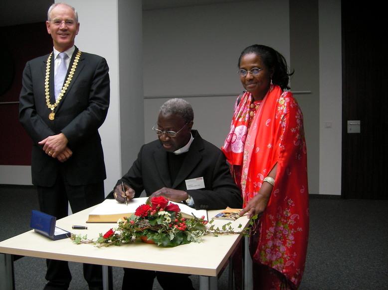 Le cardinal Sarr signe le livre d'or : le maire de la ville Dr. Siegfried Balleis, Son Emeinence le Cardinal Sarr, Dr. Pierrette Herzberger-Fofana
