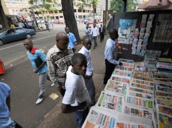 Des hommes devant un étalage de journaux, dans les rues d'Abidjan en 2008. KAMBOU SIA / AFP