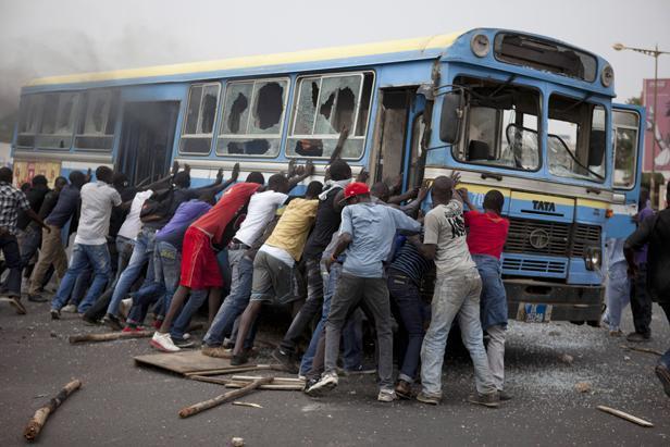 Des manifestants tentent de retourner un bus dans les rues de Dakar (Sénégal), le 1er février 2011 STRINGER / REUTERS