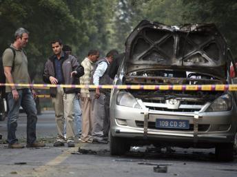Des enquêteurs examinent la carcasse de la voiture piégée à New Delhi, ce lundi 13 février 2012. REUTERS/Parivartan Sharma