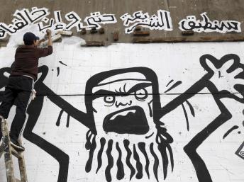 Dans une rue près de la place Tahrir, au Caire, un manifestant peint la caricature d'un Frère musulman, le 24 janvier 2013. REUTERS/Amr Abdallah Dalsh