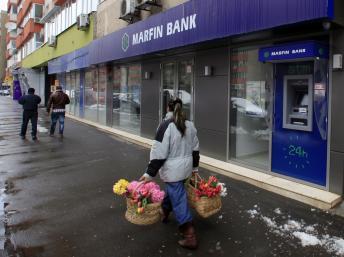 Une vendeuse de rue passe devant une agence bancaire à Bucarest, le 28 mars 2013.