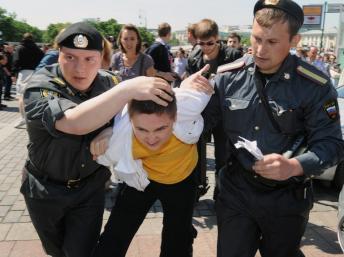 A Moscou, un manifestant homosexel malmené par deux policiers.