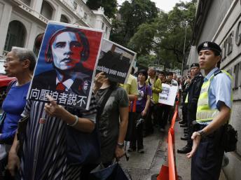 Manifestation de soutien à Snowden à Hong Kong le 15 juin 2013, des pancartes montrent le président Obama avec des écouteurs.