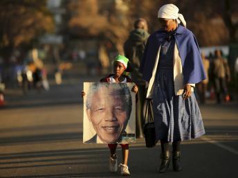 Une petite fille transportant un portrait de Nelson Mandela, non loin de la clinique où il est hospitalisé à Pretoria, le 3 juillet 2013. REUTERS/Siphiwe Sibeko