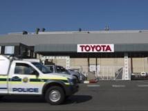 A Durban, un véhicule de police stationne devant une usine Toyota en grève, le 20 août 2013. REUTERS/Rogan Ward