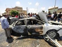 Le 6 août, à Benghazi, des passants entourent la carcasse d'une voiture détruite après l'explosion d'une bombe qu'elle transportait, tuant le conducteur. REUTERS/ Esam Omran Al-Fetori