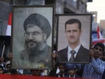 Des musulmans chiites brandissent les portraits du leader du Hezbollah, Hassan Nasrallah (g) et du président syrien Bachar el-Assad. REUTERS/Khaled Abdullah