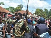 Les forces de l'ordre essayent de protéger un Nigérian accusé par la foule de rapt d'enfant, à Bissau, le 8 octobre 2013. AFP PHOTO/STG