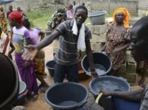 Des gens font la queue avec des seaux pour prendre un peu d'eau d'une source communale à Dakar, le 27 septembre 2013. REUTERS/Ricci Shryock