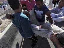 Un blessé transporté après les tirs d'une milice contre la foule venue demander son départ, le 15/11/13 à Tripoli, en Libye. REUTERS/Stringer