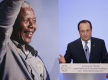 Devant un portrait géant de Nelson Mandela, François Hollande prononce son message d'ouverture du sommet de l'Elysée, le 6 décembre 2013. REUTERS/Yoan Valat/Pool