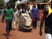 Des hommes transportent un cercueil dans une brouette dans les rues de Bangui, le lundi 9 décembre 2013. REUTERS/Emmanuel Braun