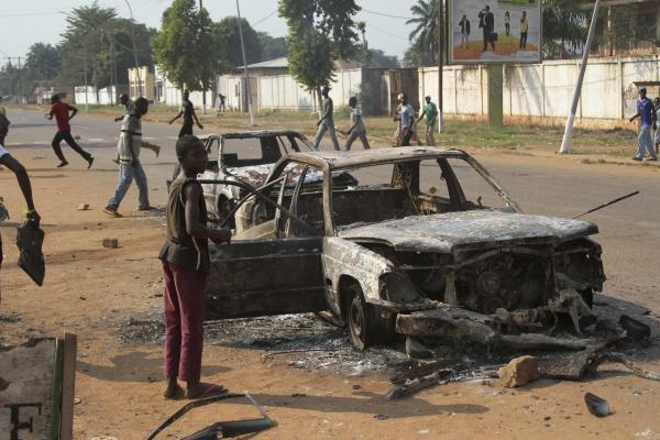 Des enfants jouent autour d'une voiture incendiée, le 20 décembre à Bangui. REUTERS/Alain Amontchi