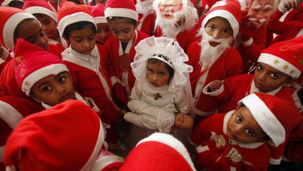 Enfants vêtus de costumes de père Noël autour d'une petite fille habillée comme la Vierge Marie lors des célébrations de Noël dans une église dans la ville indienne de Chandigarh . REUTERS/Ajay Verma