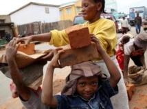 Des enfants travaillent à transporter des briques, à Antananarivo, le 19 décembre 2013. AFP PHOTO / ALEXANDER JOE