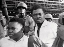 Patrice Lumumba (d.), le 30 juin 1960 à Leopoldville, aux côtés du vice-président du Sénat Joseph Okito, entourés de soldats. AFP PHOTO / STRINGER
