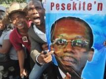Portrait d'Aristide en main, les partisans de l'ancien président haïtien sont venus en nombre manifester aux portes du tribunal, Port-au-Prince, le 8 mai 2013. AFP PHOTO Thony BELIZAIRE.