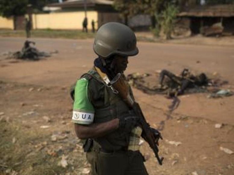Un soldat de la Misca passe devant les corps calcinés de deux musulmans tués par une foule hostile, dimanche 26 janvier à Bangui. REUTERS/Siegfried Modola