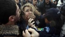 Un policier arrête une manifestante durant un rassemblement à Alger le 6 mars 2014, pour protester contre la candidature d'Abdelaziz Bouteflika pour un 4e mandat présidentiel. REUTERS/Ramzi Boudina