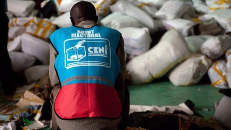 Kinshasa, 3 décembre 2011. Un agent électoral de la Céni au milieu des sacs de bulletins de vote. AFP / Gwenn Dubourthoumieu
