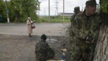 Une femme lit la Bible alors que des séparatistes pro-russes prennent position près de la ville de Slaviansk, à l'est de l'Ukraine, le 5 mai 2014.
