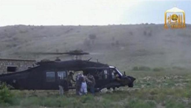 Dans cette image vidéo, on aperçoit le sergent Bowe Bergdahl (2e à droite, dos) mené vers un hélicoptère Blackhawk pendant sa libération à la frontière afghane, le 31 mai 2014.