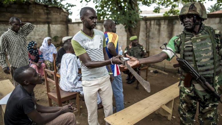 Un habitant du quartier PK5 remet sa machette à un soldat de la Misca. Bangui, le 8 juin 2014. AFP PHOTO/MARCO LONGARI