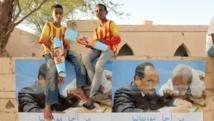 Akjout, le 18 juin 2014. Deux garçons tiennent en main des affiches de campagne du président sortant et candidat à un ssecond mandat Mohamed ould Abdel Aziz. AFP PHOTO / SEYLLOU