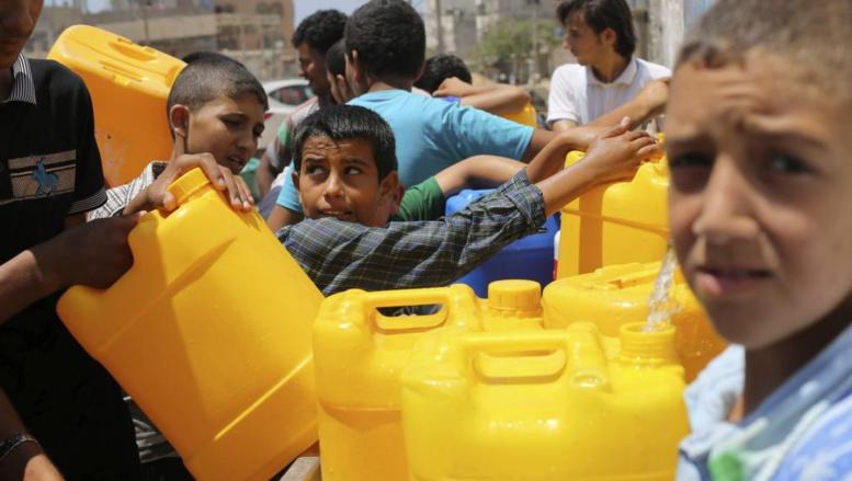 A Khan Younes (sud de la bande de Gaza) des jeunes Palestiniens profitent de la trêve humanitaire pour remplir des bidons d'eau.