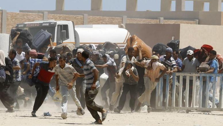 iens, lassés d'attendre, essaient de forcer le passage de la frontière tunisienne au poste de Ras Jedir, ce vendredi 1er août. Les policiers tunisiens tirent des grenades lacrimogènes pour les stopper. REUTERS/Zoubeir Souissi