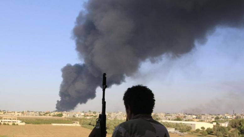 Un combattant de la milice de Zintan devant l'incendie d'un dépôt d'hydrocarbures à Tripoli, le 2 août 2014. REUTERS/Hani Amara