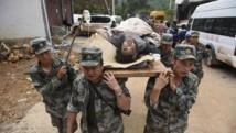 Les secours transportent, sur leurs épaules, une victime du tremblement de terre dans la province de Yunnan, le 4 août 2014.