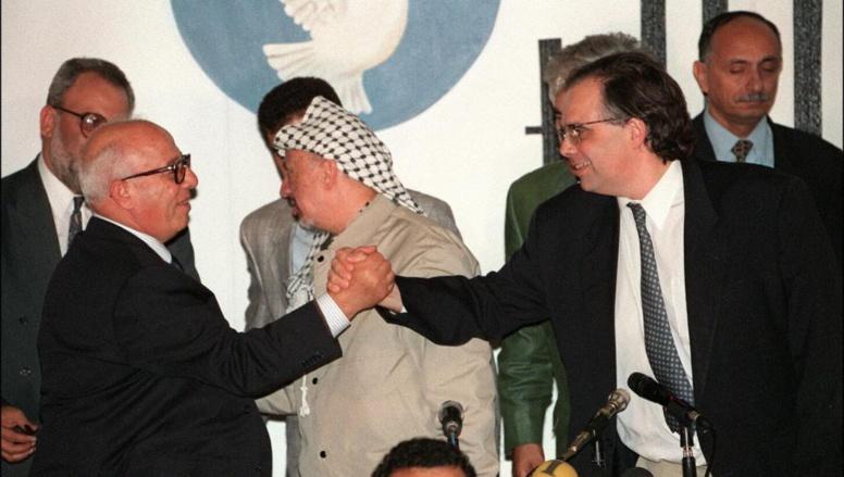 Uri Savir, à droite, sert la main du négociateur palestinien Ahmed Qorei Abu Ala, en septembre 1995. AFP/MENAHEM KAHANA