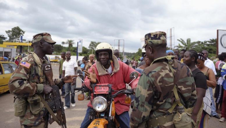 Des soldats libériens contrôlent les habitants du comté de Bomi County, le 11 août 2014. REUTERS/Stringer