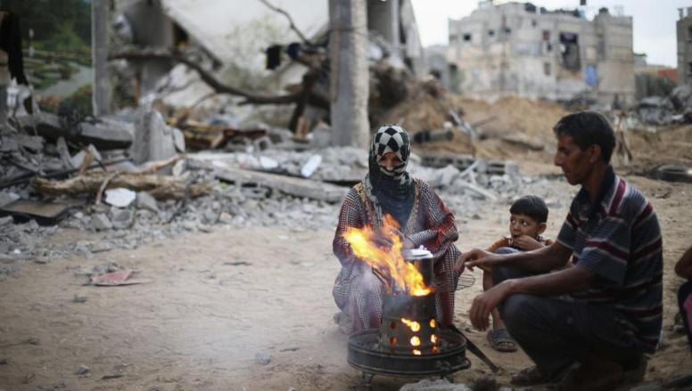 Une famille de Palestiniens prend le thé au milieu des ruines à Gaza, le 18 août 2014. REUTERS/Ibraheem Abu Mustafa