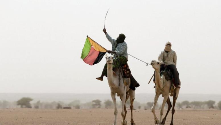Dans la région de Kidal, des touaregs brandissent le drapeau de l'Azawad, le 28 juillet 2013. AFP PHOTO/KENZO TRIBOUILLARD