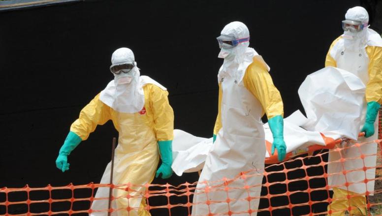 Du personnel de Médecins sans frontières porte le corps d'une personne décédée du virus Ebola, le 1er avril 2014, à Guekedou, en Guinée, dans un centre pour victimes de la fièvre hémorragique. AFP PHOTO / SEYLLOU
