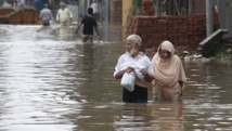 Un couple se déplace sur une route complètement submergée par les flots, le 4 septembre 2014 à Lahore. REUTERS/Mohsin Raza