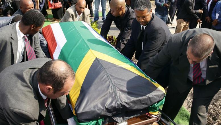 Des porteurs enterrent le cercueil contenant les restes de l'ancien journaliste Nathaniel «Nat» Nakasa au cimetière Heroes Acre le 13 septembre 2014 à Durban. AFP / Rajesh JANTILAL