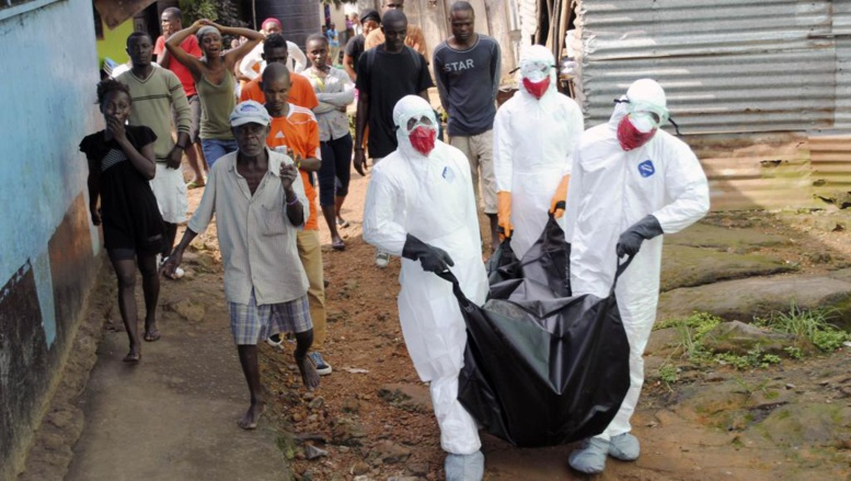 Des membres des services de santé portent le corps d'une personne morte d'Ebola, le 11 septembre 2014. REUTERS/James Giahyue