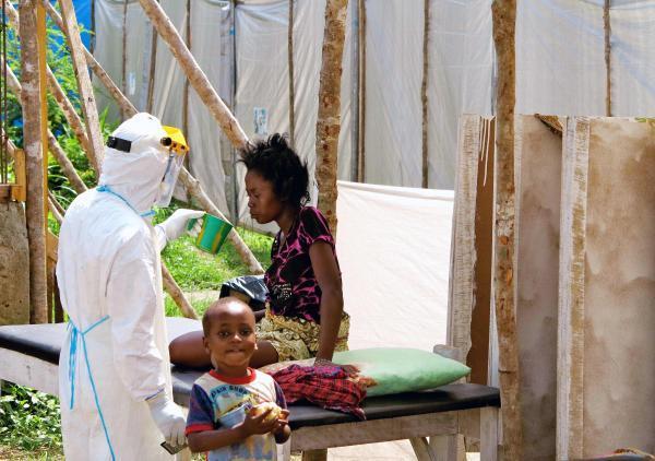 Un soignant donne à boire à une femme porteuse du virus Ebola, dans un centre de traitement spécialisé, à Kenema (Sierra Leone), en juillet 2014. REUTERS/Jo Dunlop/UNICEF/Handout via Reuters
