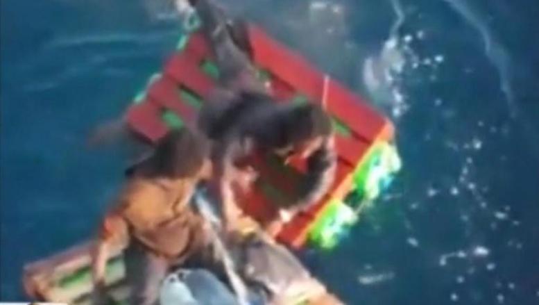 Cette image, tirée de la vidéo filmée par les marins, montre les deux personnes tentant de trouver l'équilibre sur de minuscules radeaux confectionnés par l'équipage du navire.